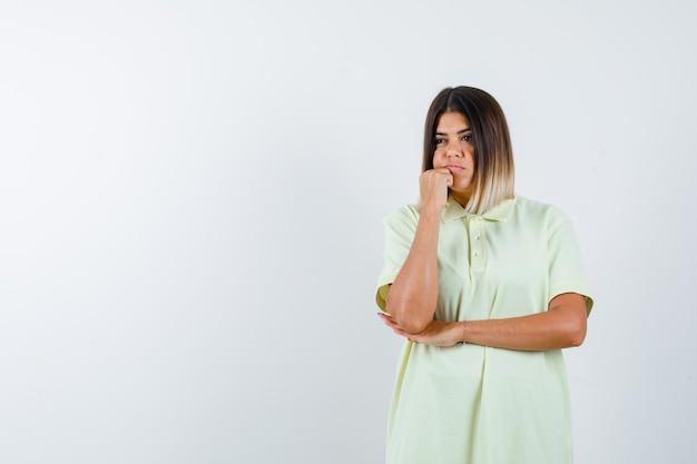 Jovem, apoiando o queixo no punho, segurando a mão sob o cotovelo na camiseta e olhando pensativa, vista frontal.