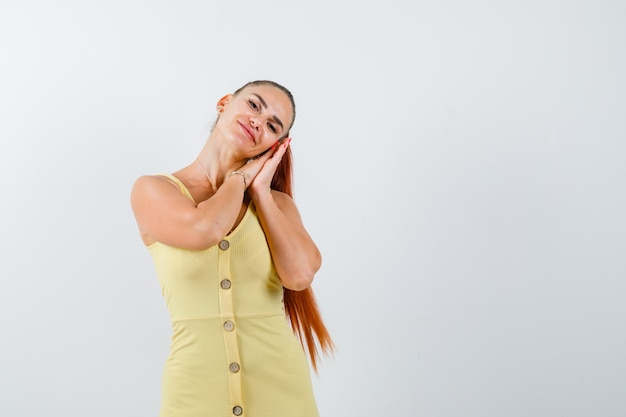 Jovem, apoiando-se nas palmas das mãos como travesseiro no vestido amarelo e parecendo relaxado. vista frontal.