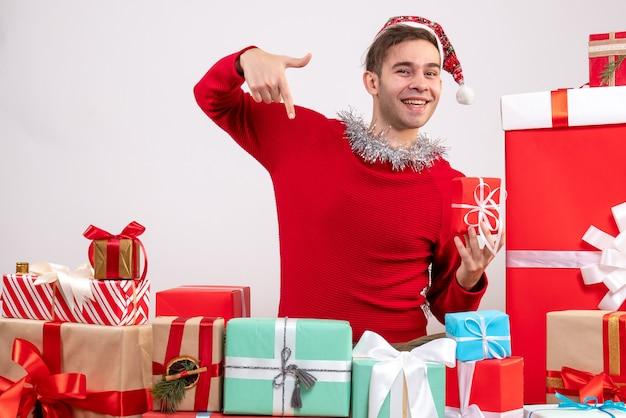 Jovem apontando com o dedo para baixo sentado em volta dos presentes de natal