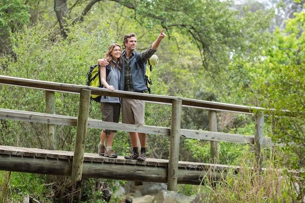 Jovem, apontando em pé com a mulher na floresta