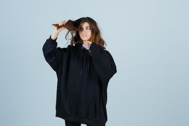 Jovem apontando o cabelo enquanto segura uma mecha de cabelo em um moletom com capuz grande, calça e olhando pensativa, vista frontal.