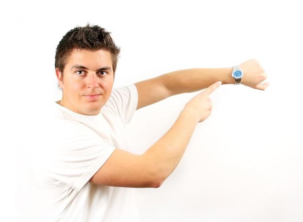 Jovem apontando o relógio de mão sobre fundo branco