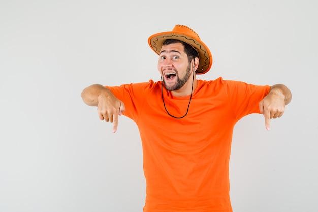 Jovem apontando os dedos para baixo em t-shirt laranja, chapéu e olhando alegre, vista frontal.
