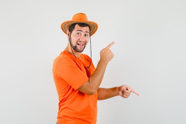 Jovem apontando os dedos para cima e para baixo em t-shirt laranja, chapéu e olhando alegre, vista frontal.