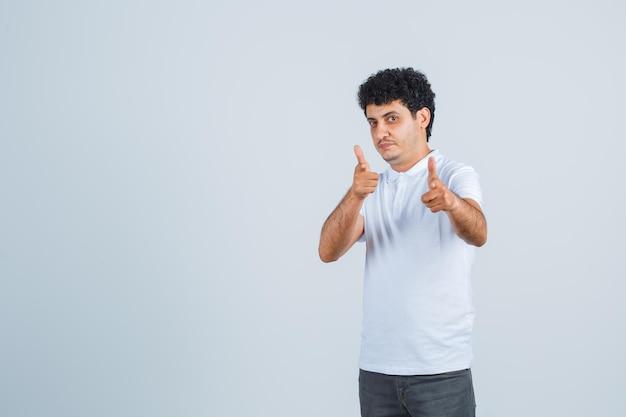 Jovem apontando para a câmera com o dedo indicador em jeans e camiseta branca e olhando sério, vista frontal.