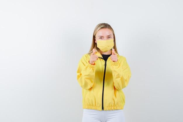 Jovem apontando para a câmera na jaqueta, calça, máscara e parecendo sensível, vista frontal.