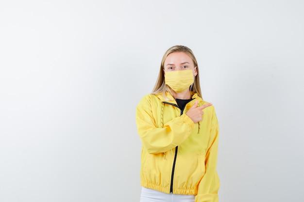 Jovem apontando para a direita em jaqueta, calça, máscara e parecendo sensata, vista frontal.