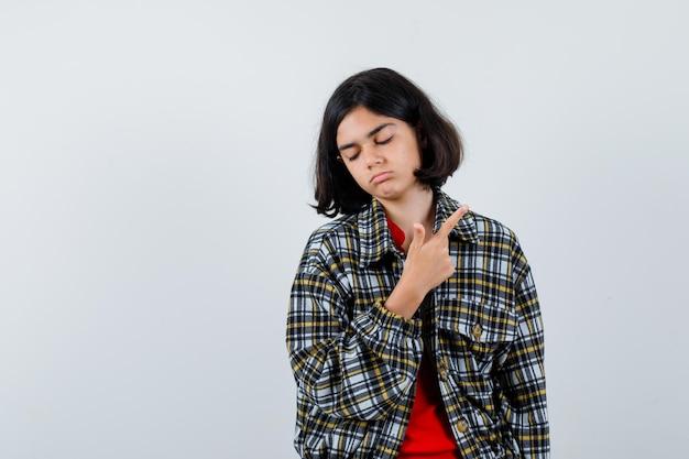 Jovem apontando para a direita, fechando os olhos com o dedo indicador em uma camisa xadrez e uma camiseta vermelha e olhando séria, vista frontal.