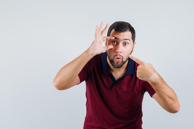 Jovem apontando para a pálpebra em t-shirt vermelha e olhando focado. vista frontal.