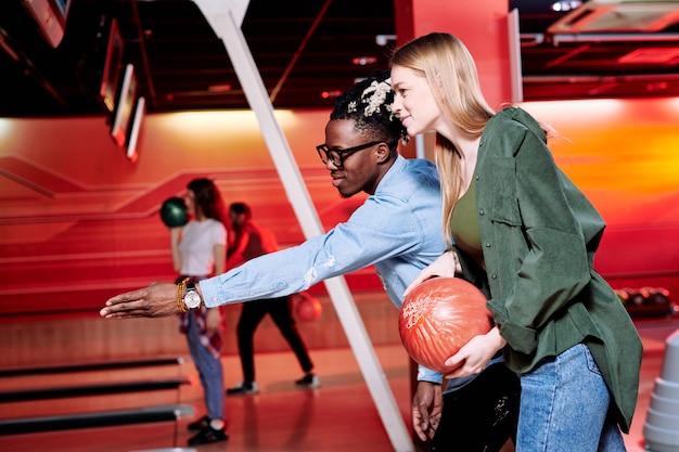 Jovem apontando para a pista de boliche enquanto explica à namorada como lançar a bola para acertar todos os boliche
