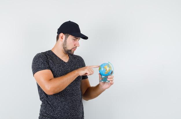 Jovem apontando para algum lugar no globo com camiseta e boné e parecendo pensativo