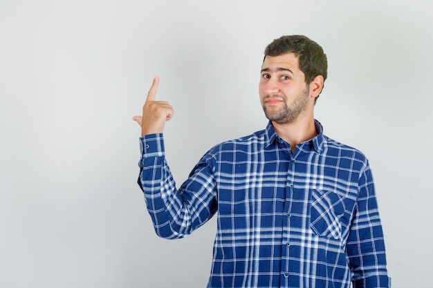 Jovem apontando para as costas e sorrindo com uma camisa xadrez