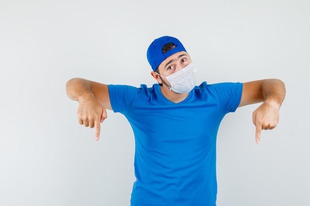 Jovem apontando para baixo com camiseta azul, boné e máscara, parecendo confiante