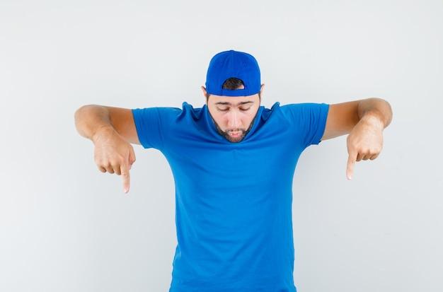 Jovem apontando para baixo com camiseta azul e boné e olhando focado