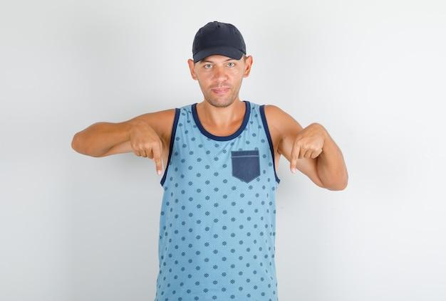 Jovem apontando para baixo com o dedo indicador em uma camiseta azul com tampa