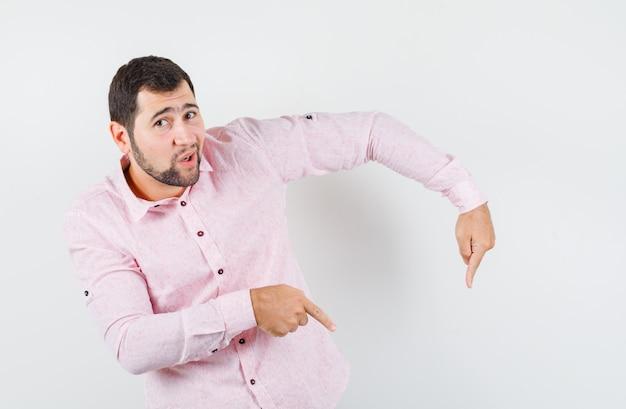 Jovem apontando para baixo com uma camisa rosa e parecendo confiante