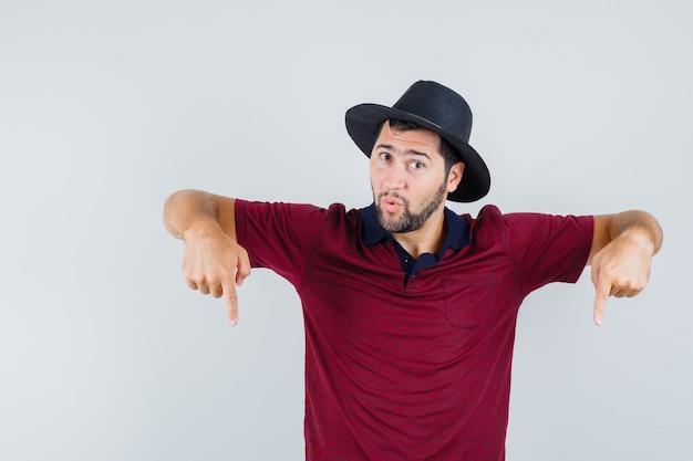 Jovem apontando para baixo em t-shirt vermelha, chapéu e parecendo surpreso, vista frontal.