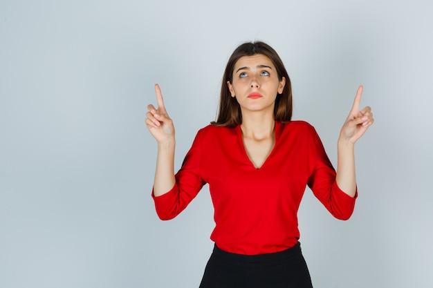 Jovem apontando para cima com blusa vermelha, saia e parecendo assustada