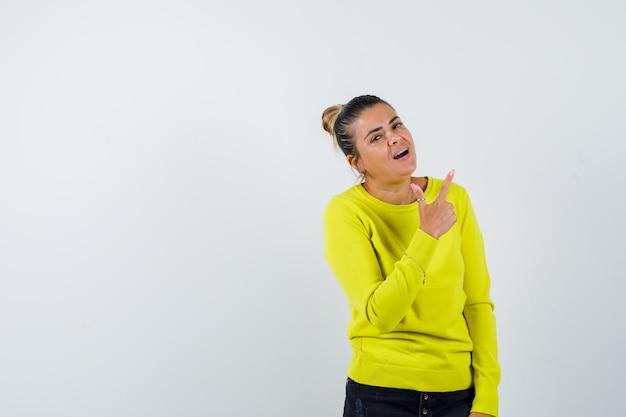 Jovem apontando para cima com um suéter amarelo e calça preta e parecendo feliz