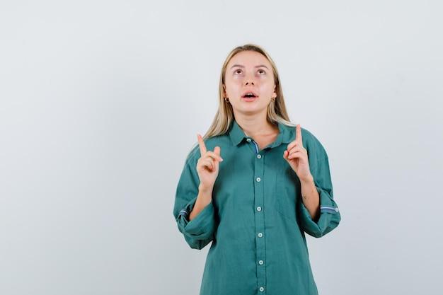 Jovem apontando para cima com uma camisa verde e parecendo esperançosa