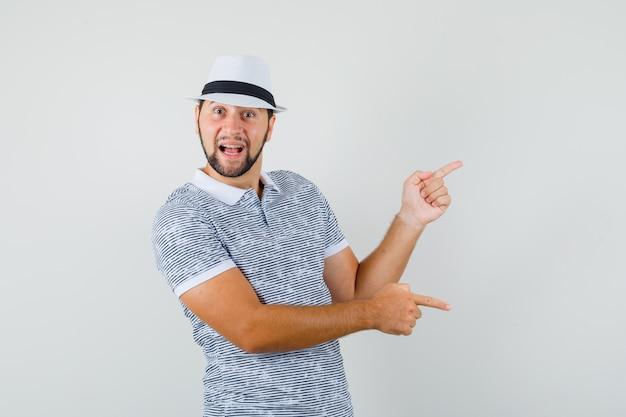 Jovem apontando para cima e para baixo em camiseta listrada, chapéu e olhando feliz. vista frontal.