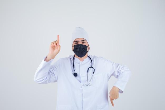 Jovem apontando para cima e para baixo em uniforme branco, máscara e parecendo confiante. vista frontal.