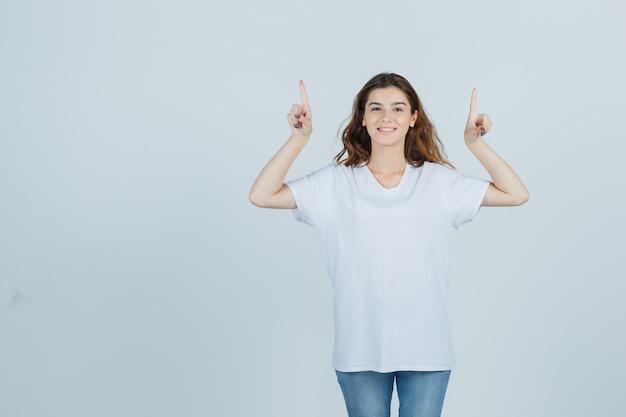 Jovem apontando para cima em camiseta, jeans e parece feliz. vista frontal.