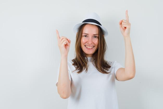Jovem apontando para cima em t-shirt branca, chapéu e olhando feliz, vista frontal.