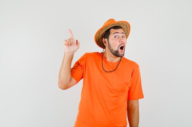 Jovem apontando para cima em t-shirt laranja, chapéu e olhando curioso, vista frontal.