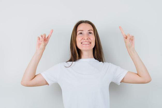 Jovem apontando para cima em uma camiseta branca e olhando alegre, vista frontal.