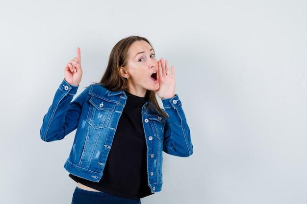 Jovem apontando para cima enquanto contava um segredo na blusa, jaqueta e parecendo curiosa, vista frontal.