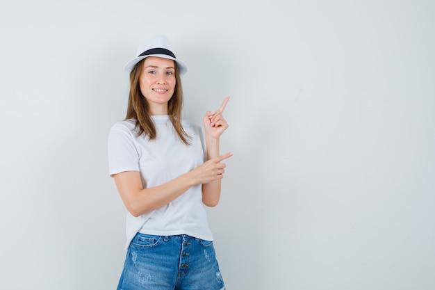 Jovem apontando para o canto superior direito em camiseta branca, chapéu, shorts e olhando alegre. vista frontal.