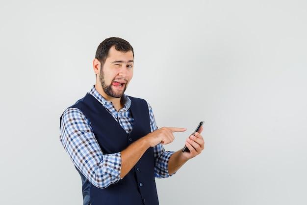 Jovem apontando para o celular, piscando os olhos, mostrando a língua na camisa, colete, vista frontal.