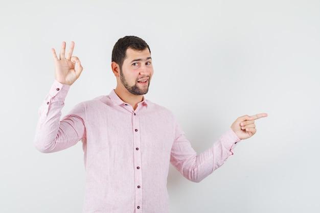 Jovem apontando para o lado com sinal ok com uma camisa rosa e parecendo confiante