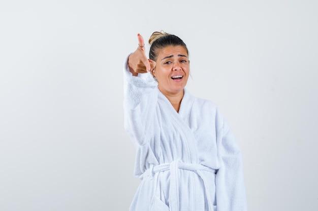 Jovem apontando para o lado com um roupão de banho e parecendo confiante