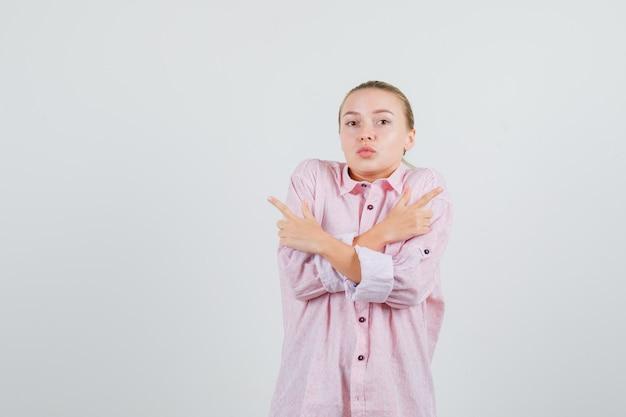 Jovem apontando para o lado com uma camisa rosa e parecendo confusa