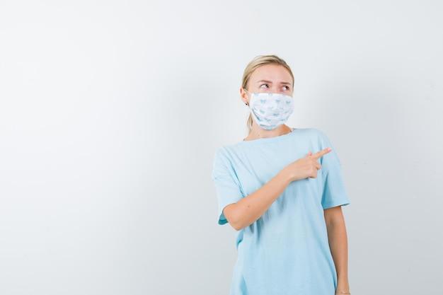 Jovem apontando para o lado direito de camiseta, máscara e parecendo pensativa