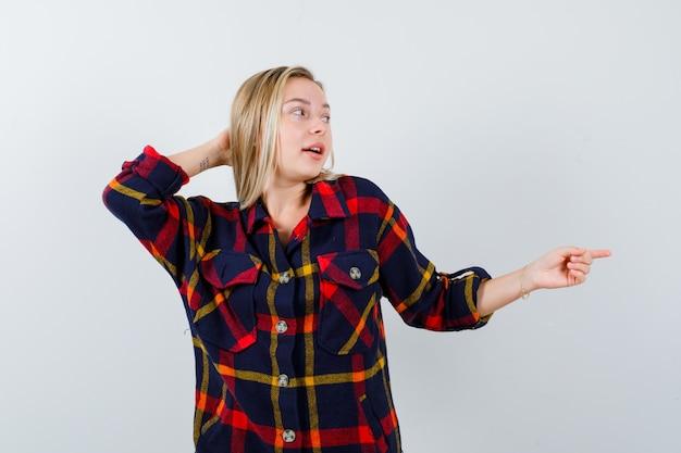 Jovem apontando para o lado direito, segurando a mão atrás da cabeça em uma camisa quadriculada e olhando feliz, vista frontal.