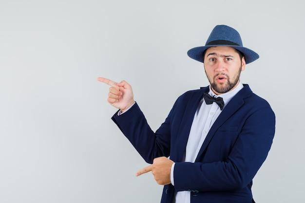Jovem apontando para o lado e para baixo no terno, chapéu e parecendo confuso, vista frontal.