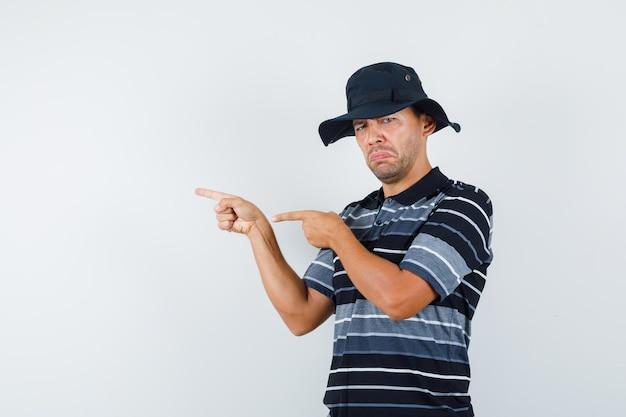 Jovem apontando para o lado em t-shirt, chapéu e parecendo triste, vista frontal.