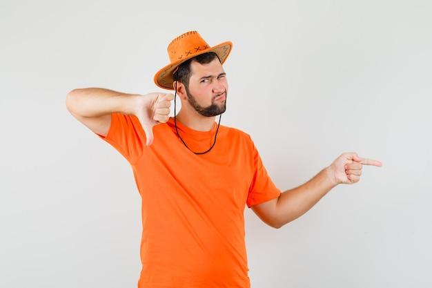 Jovem apontando para o lado, mostrando o polegar para baixo em camiseta laranja, chapéu e parecendo insatisfeito. vista frontal.