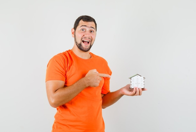 Jovem apontando para o modelo de casa em t-shirt laranja e olhando feliz. vista frontal.