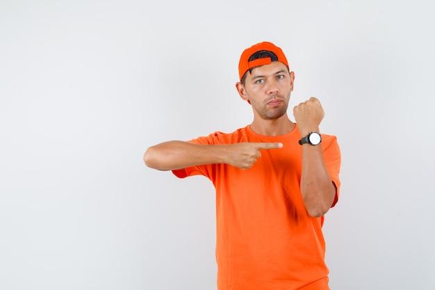Jovem apontando para o relógio de camiseta laranja e boné, sério