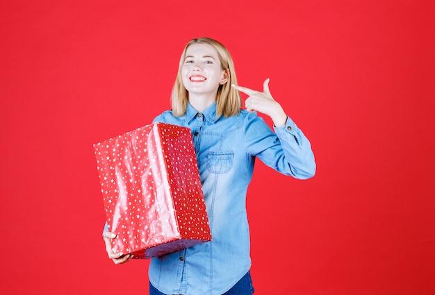 Jovem apontando para o sorriso dela e segurando um presente na parede vermelha