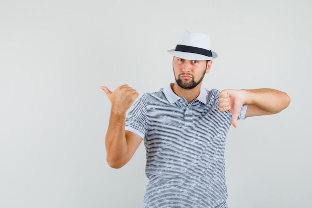 Jovem apontando para trás enquanto mostra o polegar para baixo em uma camiseta listrada, chapéu e parecendo descontente, vista frontal.