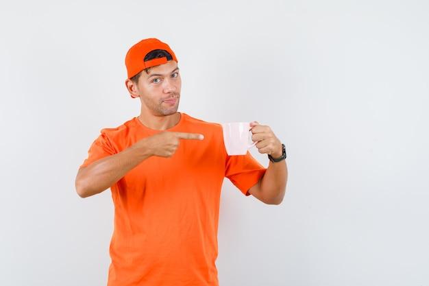 Jovem apontando para um copo de bebida com camiseta laranja e boné