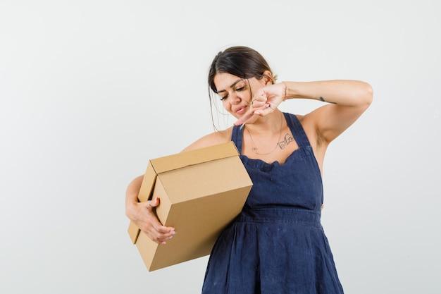 Jovem apontando para uma caixa de papelão em um vestido