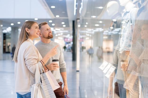 Jovem apontando para uma grande vitrine no shopping enquanto mostra a nova coleção de roupas casuais para o marido