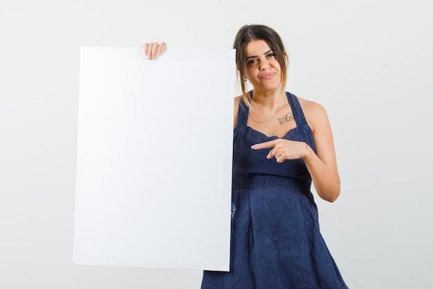 Jovem apontando para uma tela em branco no vestido e parecendo confiante