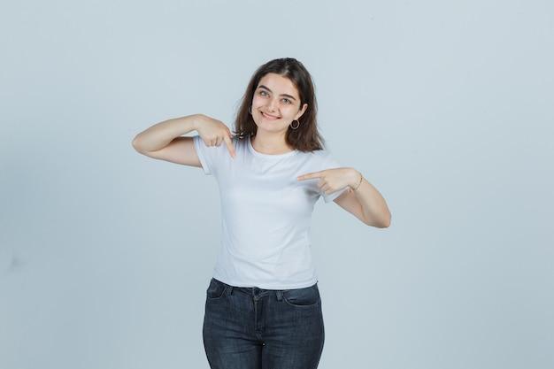 Jovem apontando-se em t-shirt, jeans e parecendo orgulhosa. vista frontal.